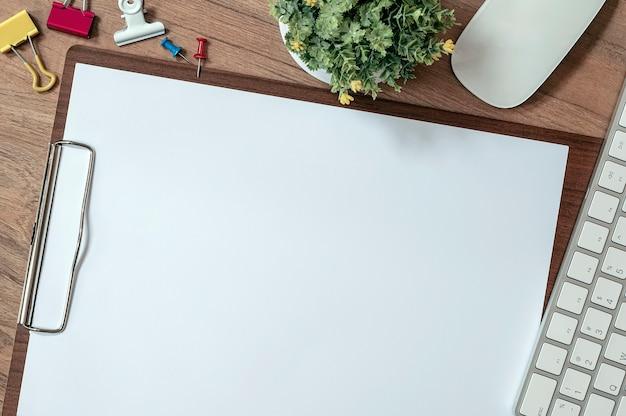 Drewniany schowek z pustym szablonem makiety papieru a4 i białą klawiaturą komputerową na drewnianym stole.