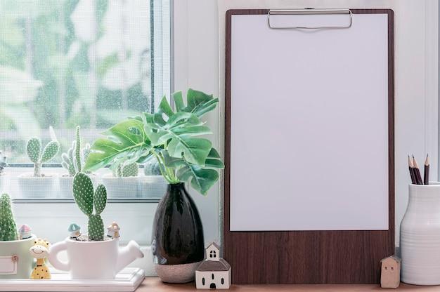 Drewniany schowek z pustym szablonem makiety papieru a4 i rośliną doniczkową na drewnianym stole.