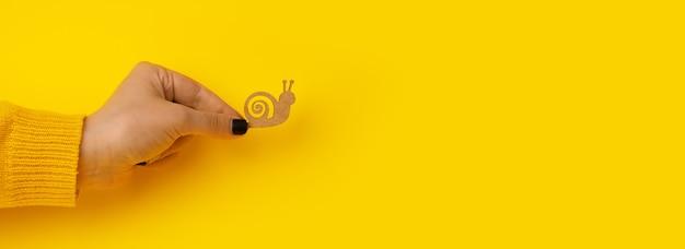 Drewniany ślimak w dłoni na żółtym tle, koncepcja powolności, makieta panoramiczna