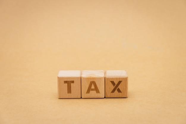Drewniany słowo podatku pozycja na tle odizolowywa. używanie jako tło biznesu