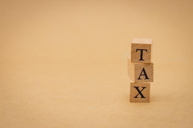 Drewniany słowo podatku pozycja na tle odizolowywa. za pomocą koncepcji biznesowej tła