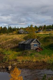 Drewniany stary dom nad rzeką, daleko za miastem, obwód murmański jesienią, krajobraz