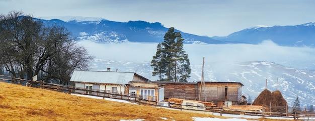 Drewniany stary dom w górach w mgłowej pogodzie