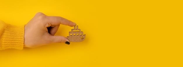 Drewniany statek w ręku na żółtym tle, koncepcja podróży lub wakacji, makieta panoramiczna