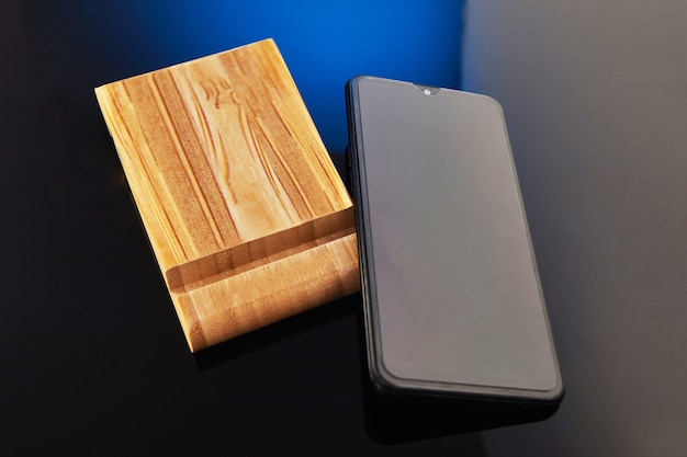 Drewniany stojak na telefon komórkowy z ręcznym telefonem