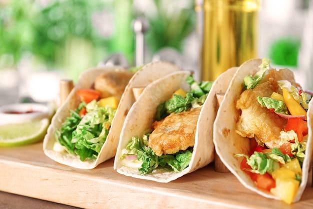 Drewniany stojak z pysznymi rybnymi tacos na kuchennym stole