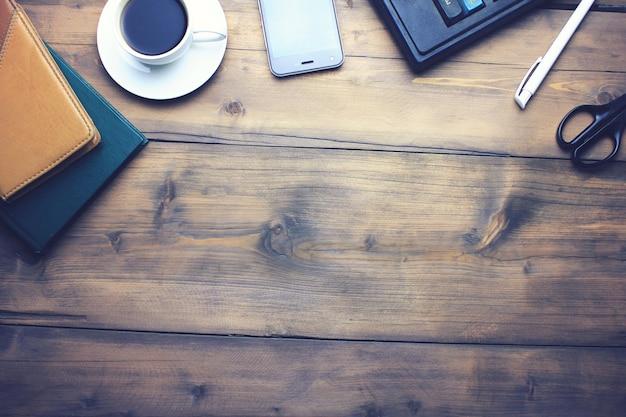 Drewniany stół biurkowy biały długopis, notatnik, smartfon, filiżanka kawy, kalkulator