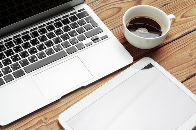 Drewniany stół biurkowy i wyposażenie do pracy z czarną kawą w widoku kątowym