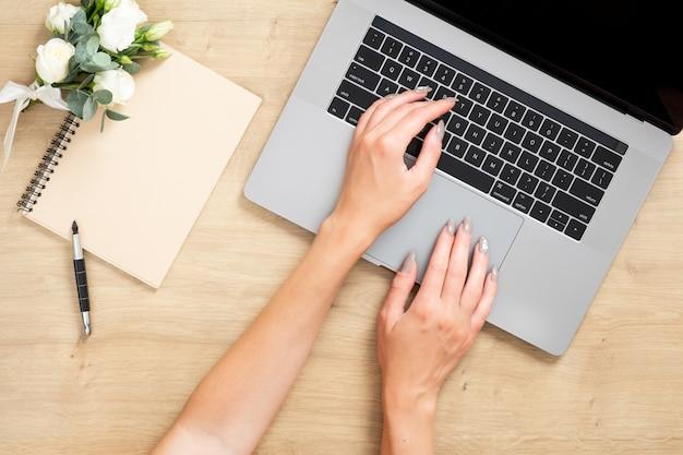Drewniany stół biurkowy z laptopem, kobiece dłonie na klawiaturze, papierowy notatnik, bukiet kwiatów.