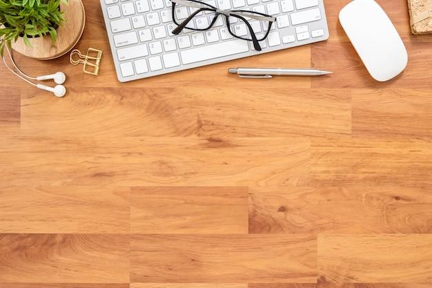 Drewniany stół biurowy z gadżetami komputerowymi i dostawami. widok z góry, płaski układ.