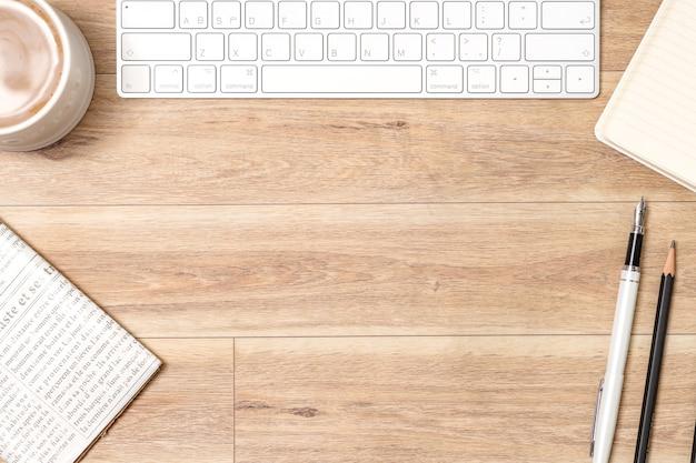 Drewniany stół biurowy z laptopem, okularami, notatnikiem, długopisem. widok z góry, kopia przestrzeń.