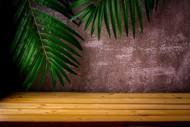 Drewniany stół do prezentacji i prezentacji produktów na pokaz, liście palmowe i ciemne chropowate tło