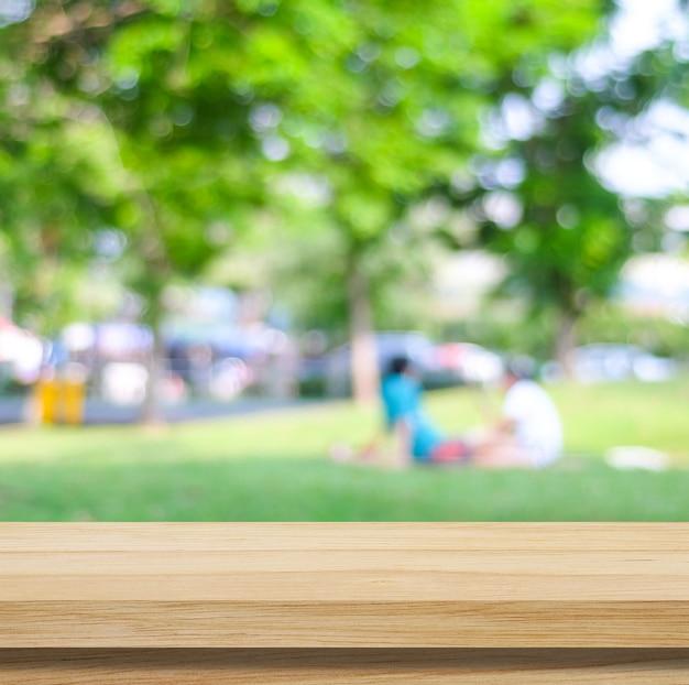 Drewniany stół do wyświetlania produktów spożywczych nad rozmytym zielonym tłem ogrodu