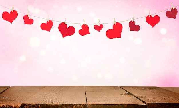 Drewniany stół i girlanda z walentynek w kształcie serc. ściana na walentynki.
