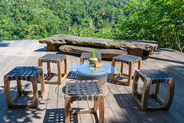 Drewniany stół i krzesła w pustej tropikalnej kawiarni obok tarasów ryżowych na bali, indonezja