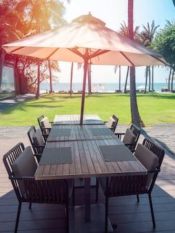 Drewniany stół i krzesła z parasolem plażowym z widokiem na morze