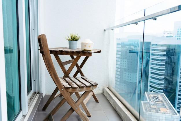 Drewniany stół i krzesło na balkonie z widokiem na nowoczesne duże miasto.