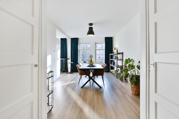 Drewniany stół i miękkie krzesła umieszczone w przestronnej jadalni w nowoczesnym mieszkaniu doświetlonym światłem słonecznym