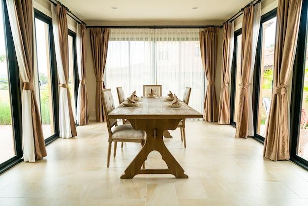 Drewniany stół jadalny w pokoju z zasłoną i oknem