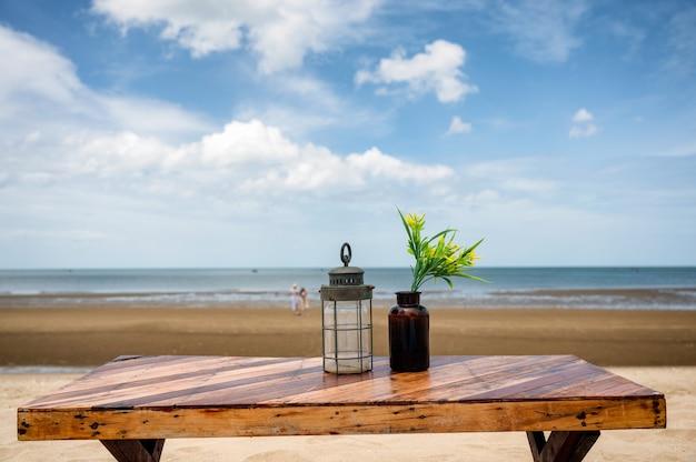 Drewniany stół jadalny z latarnią i kwiatem w szkle na plaży i błękitnym niebem w okresie letnim