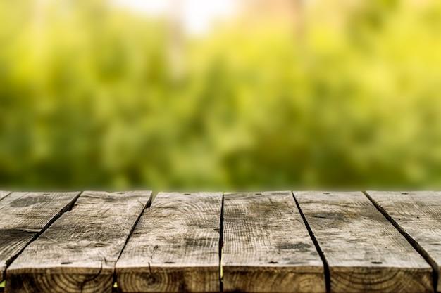 Drewniany stół lub ławka na zielonym tle niewyraźne. na dworze