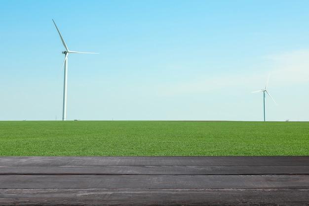 Drewniany stół na polu z wiatrakami. koncepcja rolnictwa. makieta