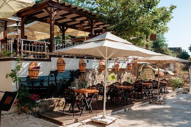 Drewniany stół na tarasie pod parasolem w plenerowym mieście side turcja. piękne meble w pobliżu starego muru na ulicy.