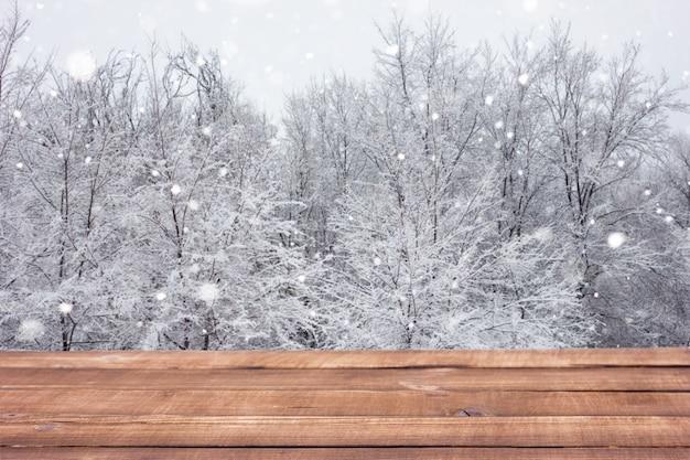 Drewniany stół na tle zimowego lasu.