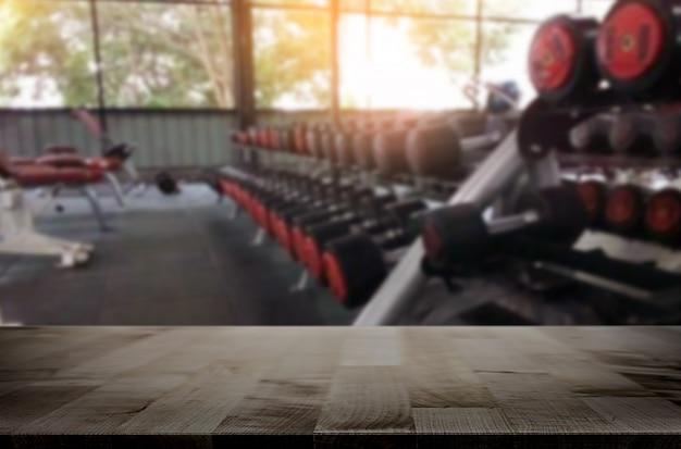 Drewniany stół na zamazanym tle sprawności fizycznej gym