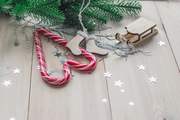 Drewniany stół pokryty cukierkami i świątecznymi dekoracjami pod lampkami