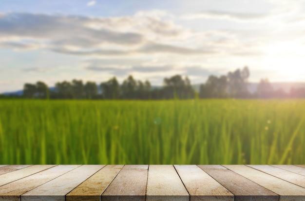 Drewniany stół przeciw ryżu pola rozmytemu tłu.