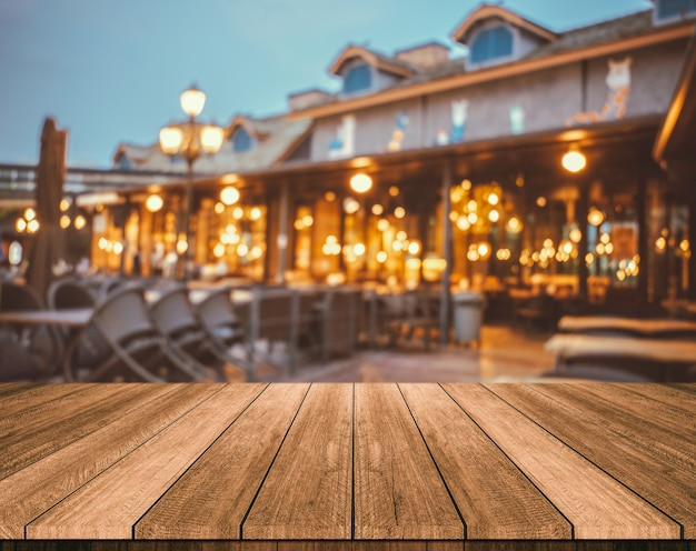 Drewniany stół przed abstrakt zamazaną restauracją zaświeca tło