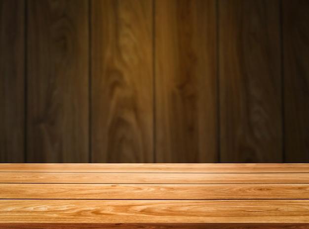 Drewniany stół przed drewnianą ścianą rozmycie tła dla makiety wyświetlania produktu.