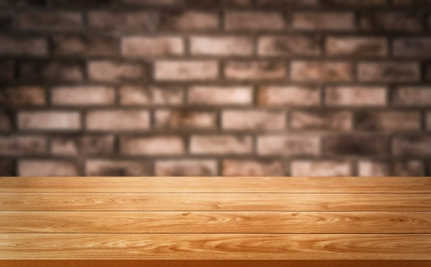Drewniany stół przed rustykalnym ceglanym murem rozmycie z pustym miejscem na kopię na stole.