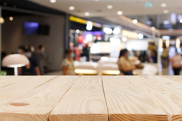 Drewniany stół przed streszczenie niewyraźne w tle centrum handlowego