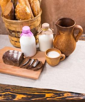 Drewniany stół przykryty koszem rustykalnego pieczywa dwie szklane butelki kremowego mleka, pół plasterki bochenka pumpernikla oraz ozdobny dzbanek i filiżanka