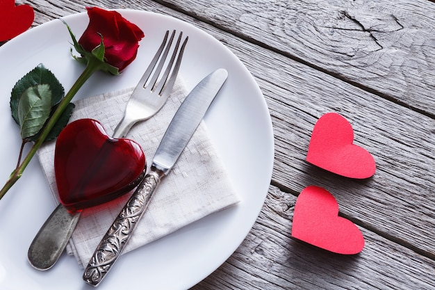 Drewniany stół restauracyjny ze szklanym sercem i różą ze sztućcami na talerzu na rustykalnym drewnie