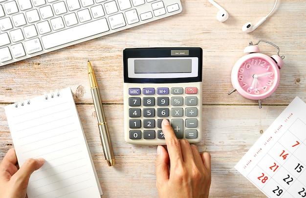 Drewniany stół roboczy klawiatura kalkulator notatnik ręka kobiety za pomocą kalkulatora leżał płasko