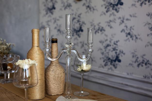 Drewniany stół służący ze szklanym świecznikiem, butelkami i kieliszkiem z kwiatami. pusta przestrzeń