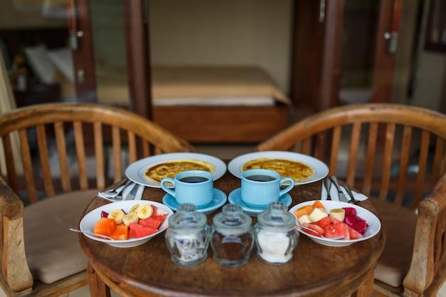 Drewniany stół ustawiony jest na tarasie pokoju. balijskie tropikalne śniadanie z owocami, kawą i jajecznicą i naleśnikiem bananowym we dwoje. na ulicy przy basenie.