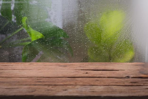 Drewniany stół w pobliżu okna w deszczowy dzień z roślinami tropikalnymi