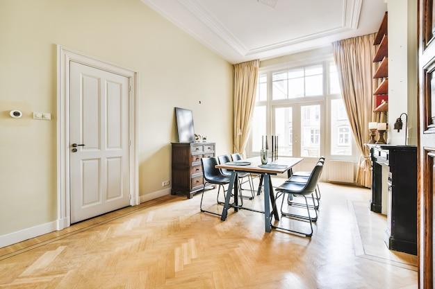 Drewniany stół z czarnymi krzesłami i dekoracją umieszczony w jasnym pomieszczeniu z dużymi oknami w eleganckich zasłonach
