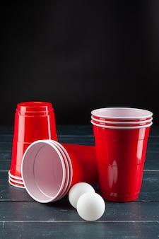 Drewniany stół z czerwonymi filiżankami i piłką do piwa