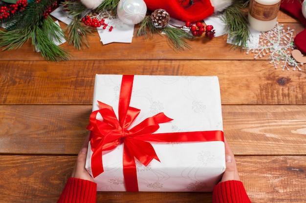 Drewniany stół z dekoracjami świątecznymi z rękami z prezentem.