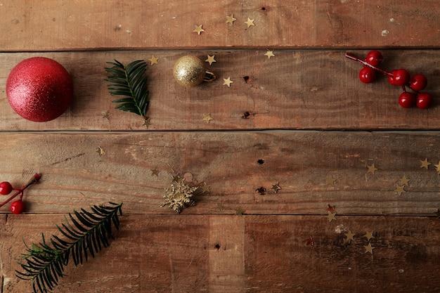 Drewniany stół z drobnymi ozdobami świątecznymi do rękodzieła ułożonymi w nieuporządkowany sposób