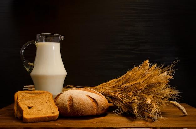 Drewniany stół z dzbanem mleka, chleba żytniego i snopa