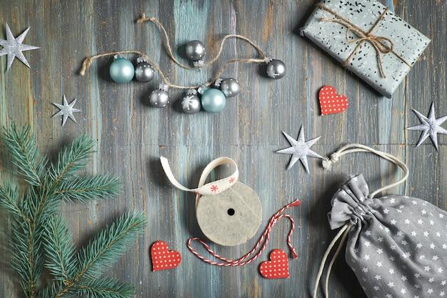 Drewniany stół z gałęzi jodłowych, zapakowanych prezentów i ozdób świątecznych