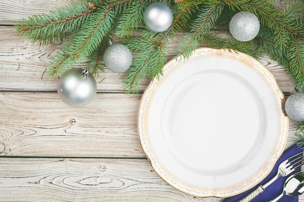 Drewniany stół z gałęzi sosny i ustawienie świątecznego stołu