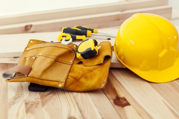 Drewniany stół z narzędziami do pracy i hełmem