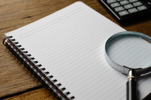 Drewniany stół z notatnikiem, okularami, lupą, długopisem, roślinami ozdobnymi. widok z góry z miejscem na kopię, układ płaski.